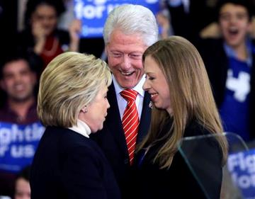 Democratic presidential candidate Hillary Clinton huddles with former President Bill Clinton and daughter Chelsea at her New Hampshire presidential primary campaign rally, Tuesday, Feb. 9, 2016, in Hooksett, N.H.
